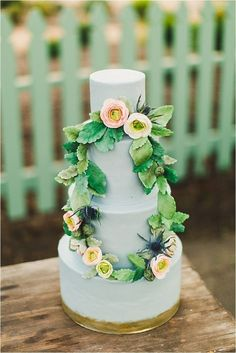 Wedding cake in pale grey blue with a draped wreath of sugar flowers.