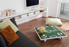 """Wer hat zu Hause schon einen zur Fußball-Couchtisch? Wenn du dein Wohnzimmer entsprechend gestalten willst, kannst du diesen Tisch ganz leicht nachbauen. Eine Holzplatte, die du schon im Baumarkt auf das gewünschte Maß zuschneiden lassen kannst, bildet die Basis des Tisches. Witzig: Die """"Füße"""" sind Fußbälle, auf denen die Tischplatte ruht. So lässt sich der Tisch nach dem Spiel schnell wieder verstauen  oder auf Balkon oder Terrasse aufbauen."""