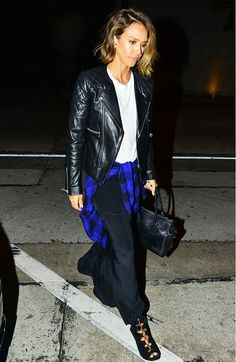 Jessica Alba wears a white t-shirt tucked into a black maxi skirt, leather jacket, plaid shirt around the waist, and lace-up wedges