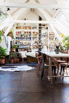 Amplio espacio abierto ático lleno de libros, descansar y espacio de comedor - diseño de biblioteca en casa