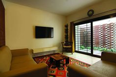 Large Living Room with carpet and Glass Door by Kamat & rozario Architecture, Architect in Bangalore, Karnataka, India