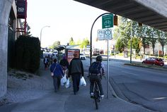 The approach to the Rupert Skytrain Station is just plain stupid. There's a bus stop, a bike route, milling pedestrians, a blind corner, a crosswalk - all thrown together with no planning and no guidance. As a result, it's down to cyclists being super careful to avoid accidents. Here, a cyclist prepares to dodge around the bus stop to avoid hitting pedestrians. Joe has had a head-on collision with another cyclist in this spot. Recently, someone has thrown in a load of gravel (on the left)…