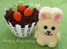 How cute! Make little carrots out of orange almond M&M's and use Mke & Ike greens for the tops and get creative with decorating cakes, cupcakes or cookies - add bunnies of any sort that are so easy to find at this time of year  (chocolate candy or marshmallow)  Shown: a cupcake with cookie or cake crumbs for dirt, Wilton picket fence wrapper, and a bunny made in a mold from white chocolate. (Found on Hungry Happenings: Almond M&M Candy Carrots)
