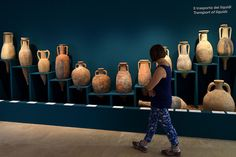 "A woman walks past amphorae used to transport liquids displayed during the exhibition ""Feeding the Empire: Tales of food from Rome and Pompei'' at Ara Pacis Museum in Rome on July 25, 2015. AFP PHOTO / TIZIANA FABI."