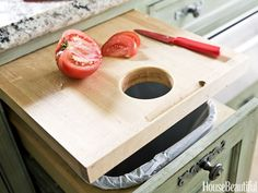 Install a Pull-Out Cutting Board for Easy Cleanup In a Houston, Texas, kitchen designed by Michele Allman, a pull-out cutting board has a hole, which makes it easy to brush the scraps straight into the trash bin just below.  Smart Kitchen Storage Ideas - Kitchen Organizing Tips - Good Housekeeping