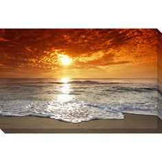 Add serenity to any room with this tranquil gallery-wrapped oversized seashore canvas. This horizontally shaped seashore canvas highlights majestic clouds engulfing a sunset with crashing waves against solid sand.