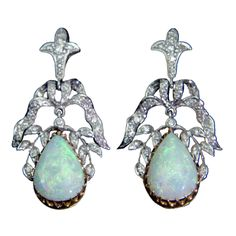 Beautiful pair of perfectly matched opal pear/teardrop shape drops, handmade and delicately framed in two-tone 14k yellow and white gold with diamonds; The colorful gemstones display an iridescent palette of pastel green, blue and peach colors; suspending from sparkling stylized bow and foliate tops, each set with thirty-one round-cut diamonds; the pair having an approx. total weight of (1) one carat.  Circa: 1950s