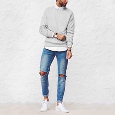 Opt for a grey crew-neck sweater and blue distressed jeans for a refined yet off-duty ensemble. Tap into some David Gandy dapperness and complete your look with white low top sneakers.   Shop this look on Lookastic: https://lookastic.com/men/looks/crew-neck-sweater-long-sleeve-shirt-jeans/21188   — White Long Sleeve Shirt  — Grey Crew-neck Sweater  — Black Leather Watch  — Blue Ripped Jeans  — White Low Top Sneakers