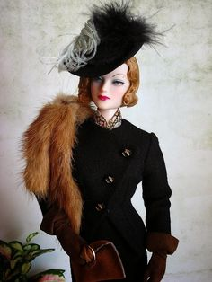 """The black felt hat from Ashton Drake's """"Doing Her Part"""" suit ensemble begs to be dressed up. The original satin ribbon band was replaced with a black velvet one and feathers accent this smart topper. OOAK suit, scarf, and gloves are from The Couture Touch, fur is from miniature furrier PD Root, and handbag is from Ashton Drake. """"C'est Moi"""" Madra Lord is from Integrity."""
