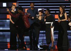 """Sharon Osborne đá một người đàn ông không rõ danh tính làm gián đoạn bài phát biểu nhận giải thưởng của dàn diễn viên trong chương trình """"The Talk"""" của bà đoạt giải ở hạng mục nhóm dẫn chương trình TV ban ngày được yêu thích nhất, tại Lễ trao giải People's Choice 2016 ở thành phố Los Angeles, California, ngày 6 tháng 1, 2016."""