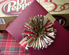 Dr pepper gift topper - how cool is this bow made from an empty soda box?  I have plenty of those.  There are a couple other cool bows made from cardboard packaging.