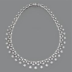 DIAMOND NECKLACE The flexible graduating row decorated with a short fringe of 68 round diamonds weighing approximately 35.30 carats, supported by 86 baguette diamonds weighing approximately 18.80 carats, mounted in 18 karat white gold, length 15½ inches.