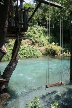 This pool is made to look like a moving river. And to top it off a tree fort with swing overlook it.