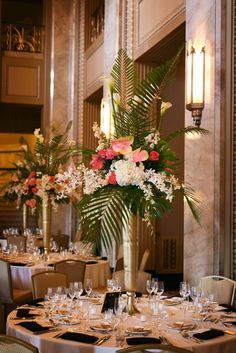 """We wanted the centerpieces to be bold and modern with large scale elements, complimentary of the scale of the room,"" Lily says. Gilded palm leaves, roses, lily of the valley and calla lilies filled tall gold vases. Quinceanera Centerpieces, Tall Wedding Centerpieces, Flower Centerpieces, Flower Decorations, Wedding Decorations, Quince Decorations, Quinceanera Ideas, Tropical Centerpieces, Greenery Centerpiece"