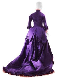 "Afternoon Dress, House of Worth (back view): ca. 1876, taffeta, machine-made lace, silk fringe, reversible colour taffeta ribbon, taffeta lining. ""Relying primarily on its pungent aniline-derived colors for impact, this otherwise unadorned asymmetrical design illustrates Maison Worth's ability to reserve its battery of decorative pyrotechnics for evening use. This gown showcases the confidence and precision that could produce equally spectacular daywear..."""