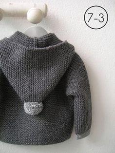 Cazadora para bebe hecho a punto bobo de color gris con capucha. Puños y pompón de capucha en gris claro y, pompones de distintos colores en cremallera. Interior en lunares.