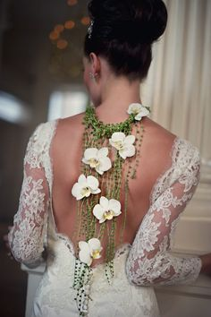 chic and beautiful necklace of flowers - draping down the back.  Love it!  As seen on facebook via A Step Above-Custom Wedding Stages.