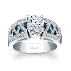 Blue+Diamond+Ring+-+6620LBDW+-+This+unique,+classic+styled,+white+gold+diamond+engagement+ring+boast+a+prong+set+round+center+diamond.++A+row+of+channel+set+blue+diamonds+artfully+encased+by+white+gold+bars+adorn+the+side+shoulders+while+pave+set+diamond+grace+their+edges+and+a+milgrain+finish+adds+the+final+touch+of+elegance. Also+available+in+18k+and+Platinum.