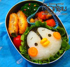 Fat Penguin Omusubi Bento    Japanese rice decorated using cut seaweed. Nose is corn. Cheek is thin sliced carrot. Serve with green leaf, tomato, and broccoli.