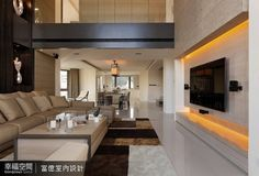 六米高度設計的電視牆以削光石材搭配木皮,在棉麻材質窗紗的光線調節中,營造溫潤的空間質感。