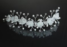 This delicate wedding hair vine is made of silver tone wire, glass crystals, pretty silk ivory organza roses and ivory pearls. It can be shaped