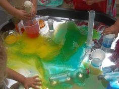 """Coloured water for pouring, measuring & colour mixing on a reflective sheet in the tuff spot, at Childminding Watford Playful Minds ("""",)"""