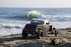 A surfer rides a wave in the distance as a jalopy takes to the sand.