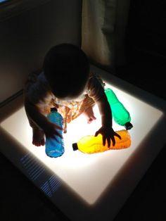 Jugando en una mesa de luz con botellas de colores #experiencias