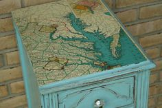 To refinish an old table top, ModPodge an old map to it.