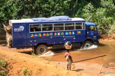 lady looks on as Aminah our ploughs through the river! Photo from passenger Simon Ottner. Overland Truck, Guinea Bissau, Sierra Leone, West Africa, Kitty, Trucks, River, Lady, Little Kitty