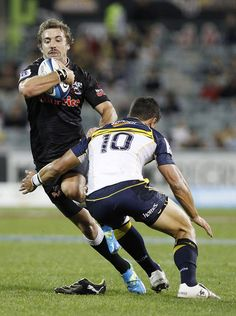 Tim Whitehead of the Sharks is tackled by Matt Toomua of the Brumbies during the round six Super Rugby match between the Brumbies and the Sharks at Canberra Stadium on March 2012 in Canberra, Australia. Matt Toomua, Manu Tuilagi, Leicester Tigers, Super Rugby, Rugby Men, Man Of The Match, Beefy Men, Sharks, Champion