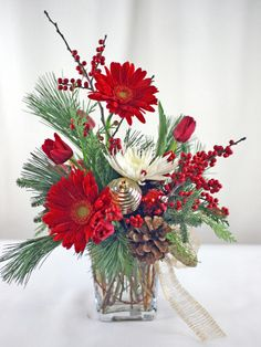 Gerbera Daisies, Tulips, and berries pop against Evergreen branches and Pinecones.  This beautiful arrangement is perfect for a hostess gift, christmas gift, or holiday decoration.  Flowers by A Floral Affair - www.afloralaffair.com.  #christmasflowers #decorations