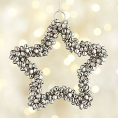 Tiny silver jingle bells are hand strung onto a wire star to craft this sweetly ringing ornament.