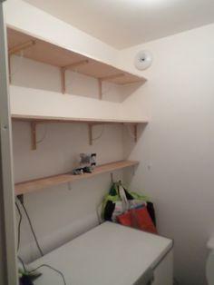Pose d'étagères dans les WC au-dessus du congélateur