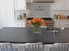 Combination of soapstone countertops and a white counter top with tile backsplash