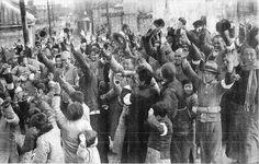 これは日本軍の入城式の日(1937年12月17日)に、食糧やタバコの配給を受け、 歓声をもって迎える南京市民ら。市民がつけている日の丸の腕章は、民間人に化けた 中国兵ではないことを証明するために、日本軍が南京市民全員に配ったものである (毎日版支那事変画報 1938.1.11発行)
