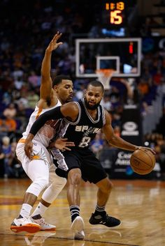 PHOENIX, AZ - FEBRUARY 21: Patty Mills #8 of the San Antonio Spurs handles the ball guarded by Phil Pressey #25 of the Phoenix Suns during the second half of the NBA game at Talking Stick Resort Arena on February 21, 2016 in Phoenix, Arizona. The Spurs defeated the Suns 118-11