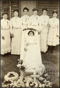 Teen Girl with Friends  Teen girls, all dressed in white, pose with the casket of their friend / sister. Several of them are holding white handkerchiefs.  Gelatin silver print, circa 1900.