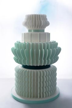 Sea green and white fondant ruffled trim are affixed around this wedding cake for a unique 3D look.