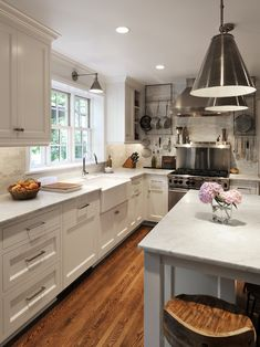 Love a bright white kitchen...source: Alethea Sadowski  Charming kitchen with sage green walls paint color, white glass-front kitchen cabinets, polished black granite countertops, subway tiles backsplash and oak hardwood floors.