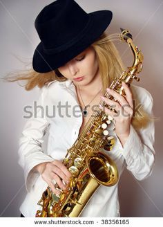 Wind is messing up hair of the beautiful girl with saxophone by Tassh, via Shutterstock