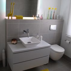 A simple, modern grey bathroom with a handle less Faeber vanity furniture unit and matt white StoneKast sit on bowl.
