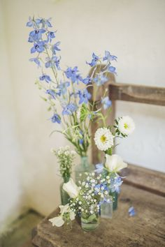 Glass jars & bottles filled with blue & white wild flower stems - Image by Matt Ethan Photography - Bride wears a Sincerity Bridal gown at a rustic outdoor wedding in Norfolk with nautical colour scheme.