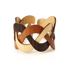 TRINITY WOODEN CUFF...This eye-catching cuff cuts against the grain of traditional jewelry design--instead of metal or plastic, it's crafted from natural hardwoods. The interlocking bands get their distinct colors not from artificial dyes or paint, but from the varieties of wood that are used: Cherry, Walnut and Wenge.