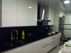 Cocina con puertas lacadas blancas y encimera y aplacados frontales en silestone negro estelar. Piso Platja d' aro, Girona.