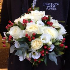 White Rose and Red Hypericum Brides Wedding Bouquet. A lovely simple yet effective winter bouquet. Liverpool, UK.