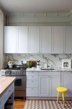 marble kitchen; yellow stool; chevron rug; white cabinets