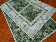 This quilted batik table runner features a floral print for the blocks in pretty shades of green, aqua, and gray, with subtle bits of turquoise and lavender. A tonal aqua print frames each block and the narrow inner border adds a touch of magenta in a stripe-y geometric print. The outer border is a beautiful leaf print in aqua with gray and lavender. The size is approximately 15 X 46 (38 X 117 cm) - a versatile size for use on a dining table, buffet, coffee table or a bedroom dresser.  I…