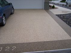 Here is another idea to incorporate the aggregate concrete into the driveway, place a band around the edge of the existing concrete driveway? So it ties in with the the front entrance and backyard paths.