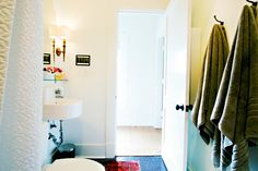 Cute Powder Room Idea  Floor: Generic black penny tile/charcoal grout  Mirror: PB Teen  Sconces: Hudson Valley Lighting  Glass shelf: IKEA  Sink: IKEA  Toilet: Toto  Fixtures: Kohler  Shower curtain: IKEA, then custom sewn and monogrammed  Rug:eBay  Stool: Vintage  Hooks: The Hook Lady  Art: Lot 9 Press, Lisa Congdon, various Chaos